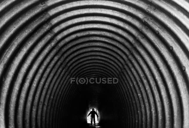 Túnel de pedestre com a silhueta do homem — Fotografia de Stock