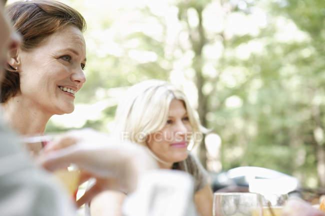 Mulher sentada a uma mesa em um jardim . — Fotografia de Stock