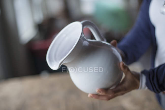 Woman holding a white pottery jug — Stock Photo