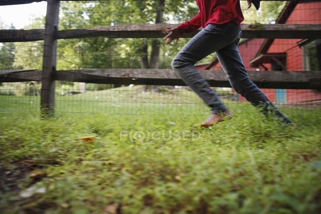 Niño corriendo por un potrero - foto de stock