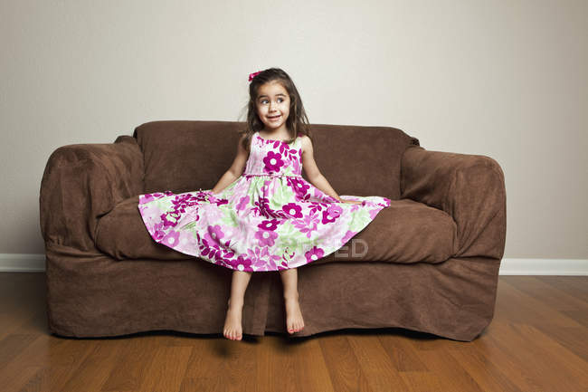 Girl sitting on a brown sofa. — Stock Photo
