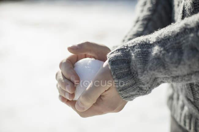 Чоловік тримає великий сніжний ком — стокове фото