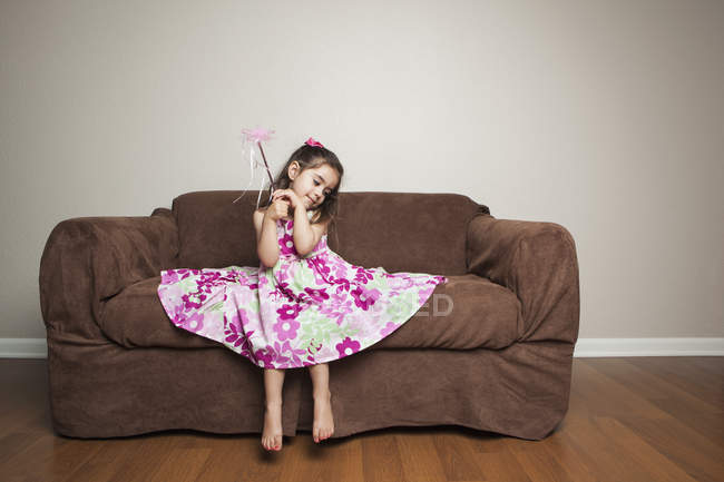 Girl in flowered dress waving a wand. — Stock Photo