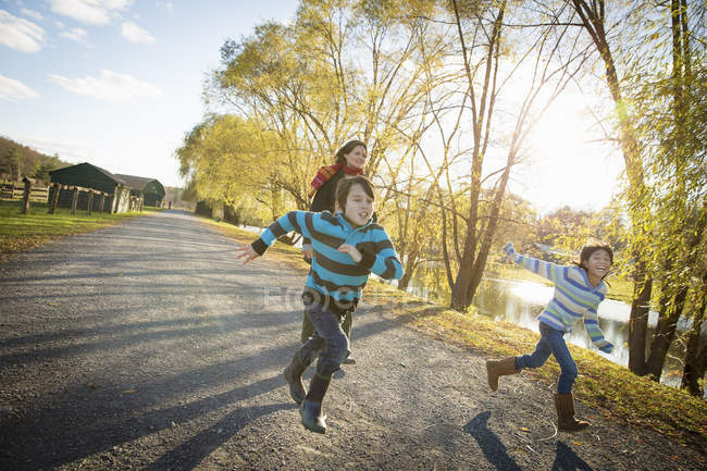 Woman and children running by a lake — Stock Photo