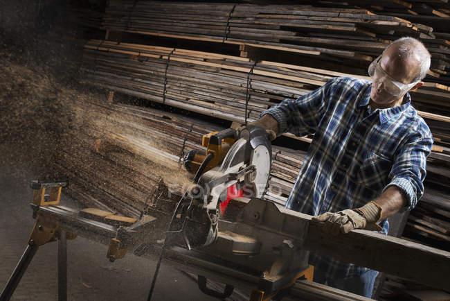 Uomo con una sega circolare per tagliare legname — Foto stock