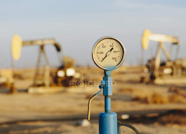 Air pressure gauge, oil rigs in background — Stock Photo