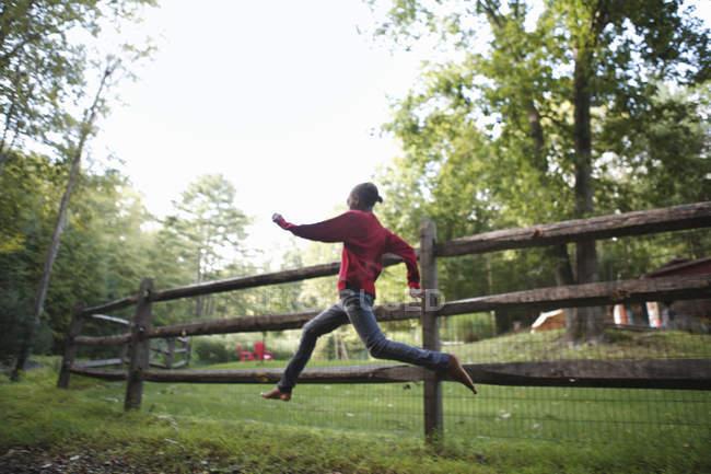 Мальчик, бег вокруг загон — стоковое фото