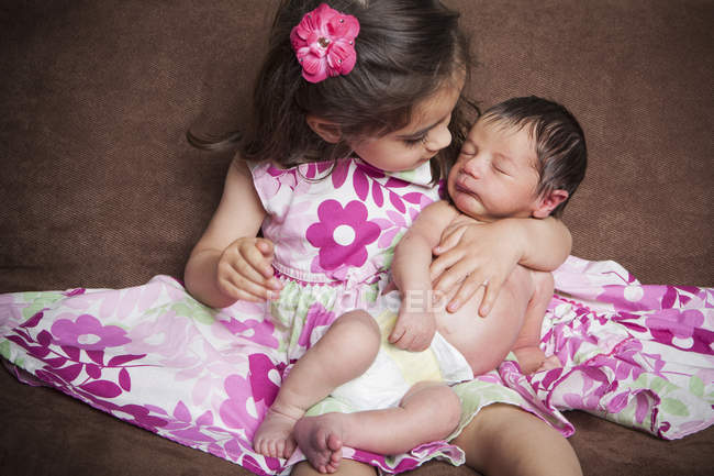 Little girl holding a newborn baby — Stock Photo
