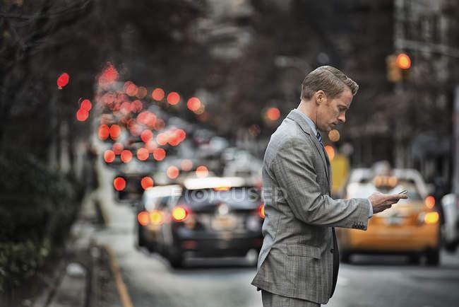 Hombre de pie en una calle concurrida al atardecer . - foto de stock