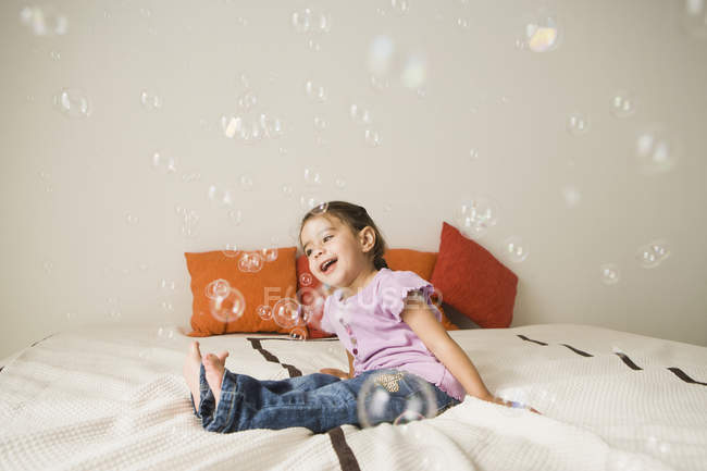 Girl on a bed laughing with soap bubbles — Stock Photo