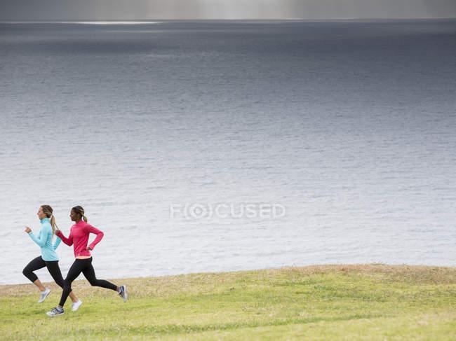 Женщины бегают по побережью . — стоковое фото
