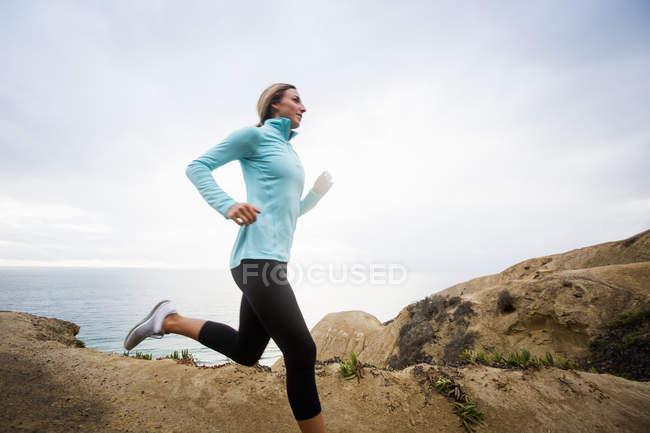 Femme jogging le long de la côte . — Photo de stock