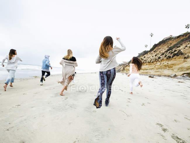 Uomini e donne che corrono su una spiaggia — Foto stock