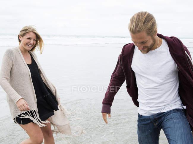 Casal caminhando em uma praia — Fotografia de Stock