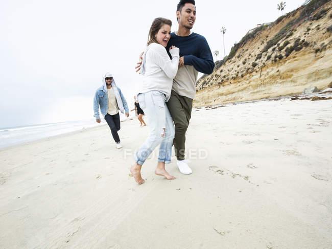 Мужчины и женщины бегут по пляжу — стоковое фото