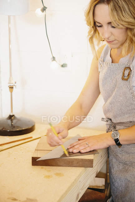 Woman in her workshop using a template — Stock Photo