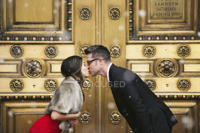 Couple kissing in front of doors — Stock Photo