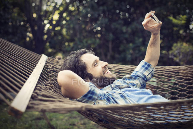 Man lying in a large hammock — Stock Photo