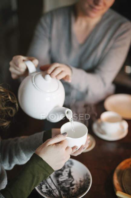 Frau Tee aus einer Teekanne gießen — Stockfoto
