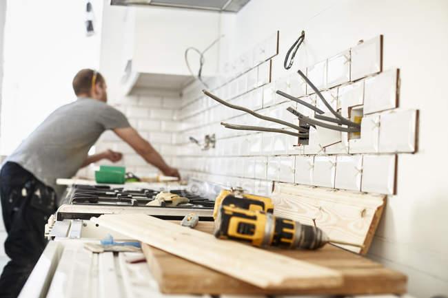 Чоловік працює на новий кухні — стокове фото