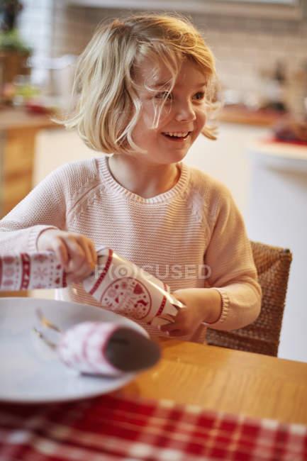 Девушка открывает рождественский крекер — стоковое фото