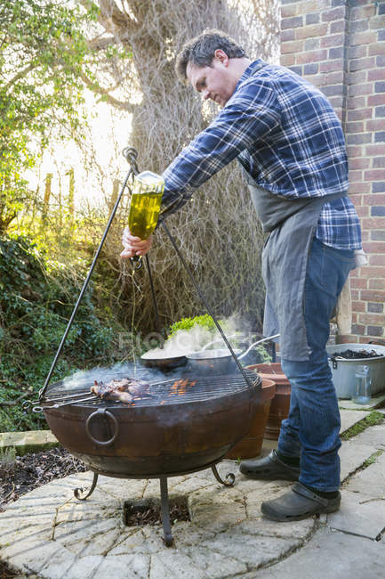 Man roasting game birds over fire — Stock Photo