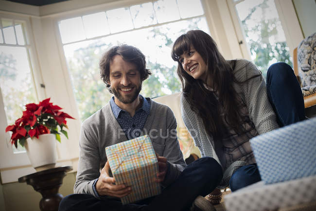 Couple exchanging wrapped presents. — Stock Photo