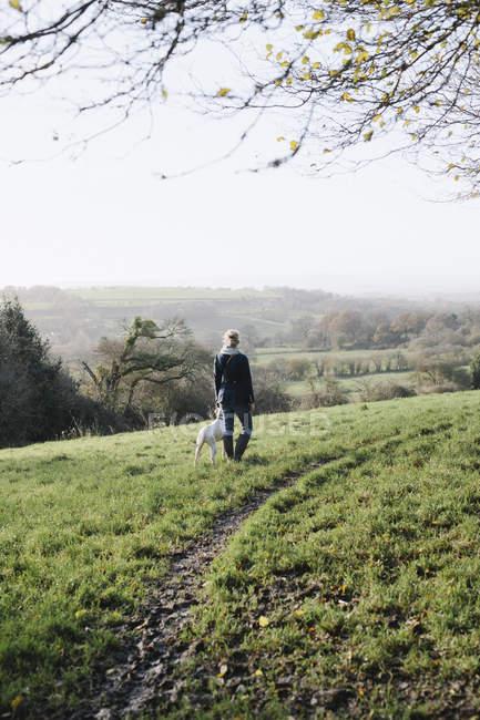 Mulher andando com um cachorro — Fotografia de Stock