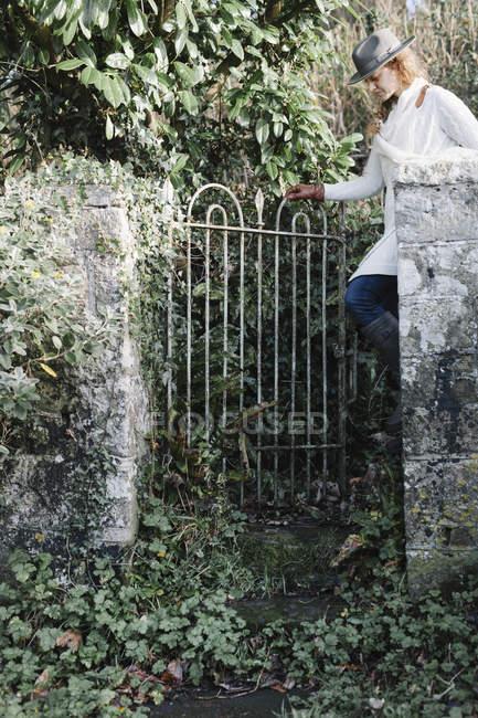 Frau ein Gartentor öffnen — Stockfoto