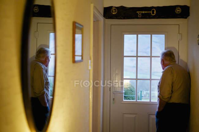 Пожилой человек, стоящий у двери — стоковое фото