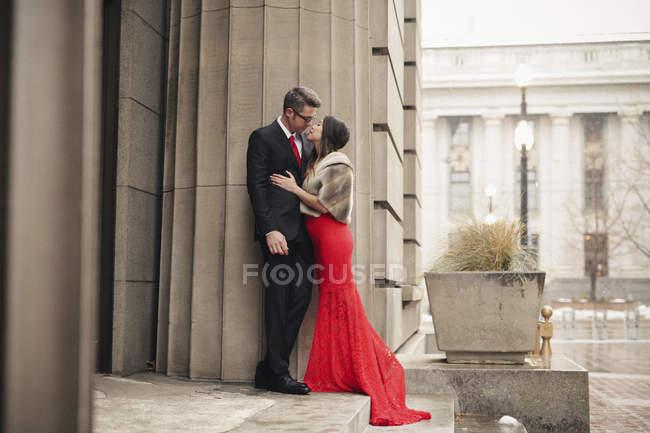 Coppie che baciano sui gradini di un edificio. — Foto stock