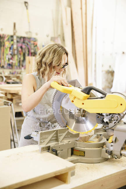 Woman woodworker using a mechanical saw — Stock Photo