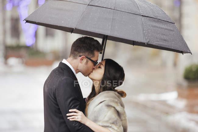 Couple embrasser sous un parapluie . — Photo de stock