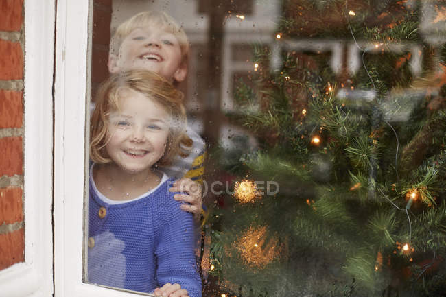 Children looking out of a window — Stock Photo