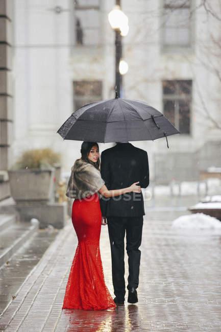 Coppie che camminano attraverso una città. — Foto stock