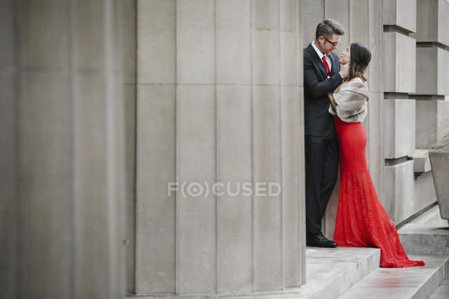 Coppie che abbracciano sui gradini di un edificio. — Foto stock