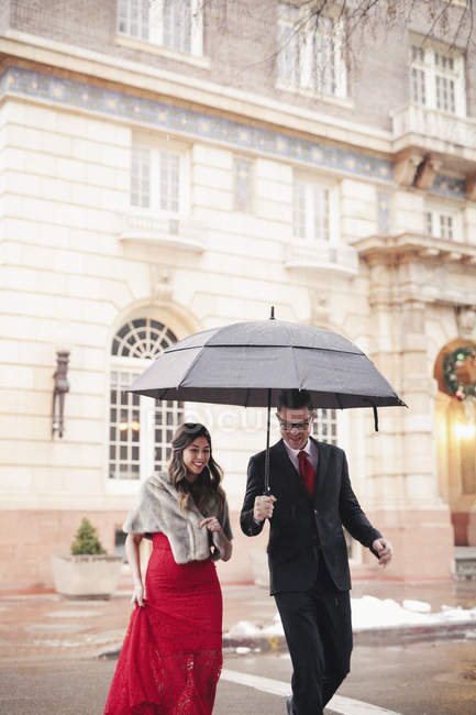 Casal caminhando através da neve na cidade . — Fotografia de Stock