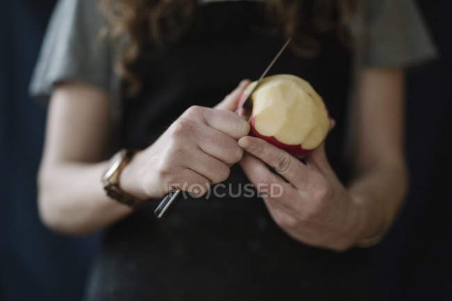 Woman peeling an apple with a knife. — Stock Photo