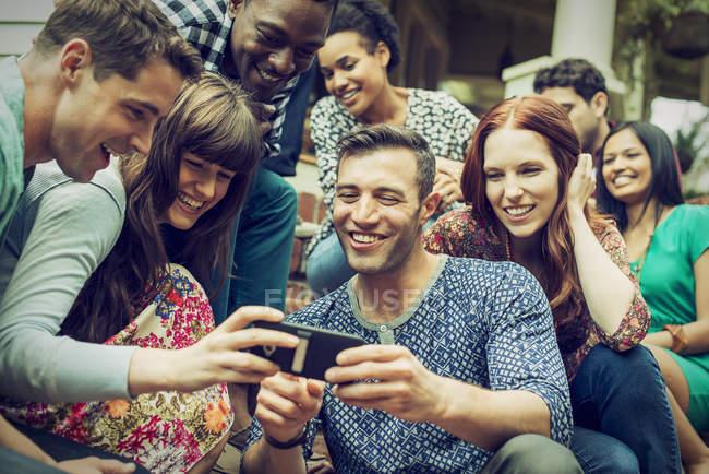 Amis regardant un téléphone intelligent — Photo de stock