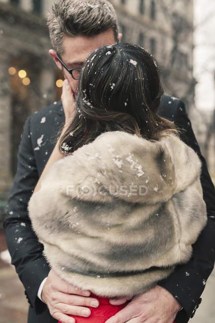 Verliebte küssen sich im leicht fallenden Schnee — Stockfoto