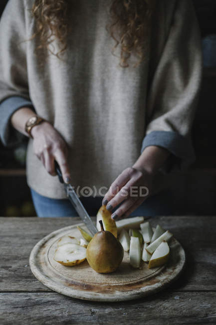 Woman slicing fresh pears — Stock Photo