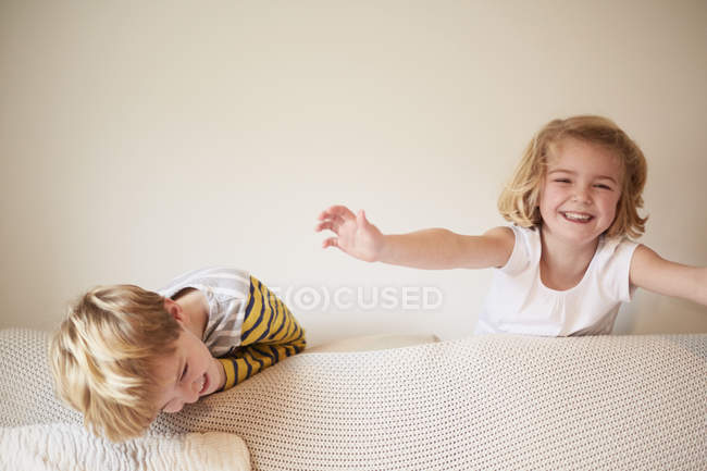 Children playing behind a sofa — Stock Photo