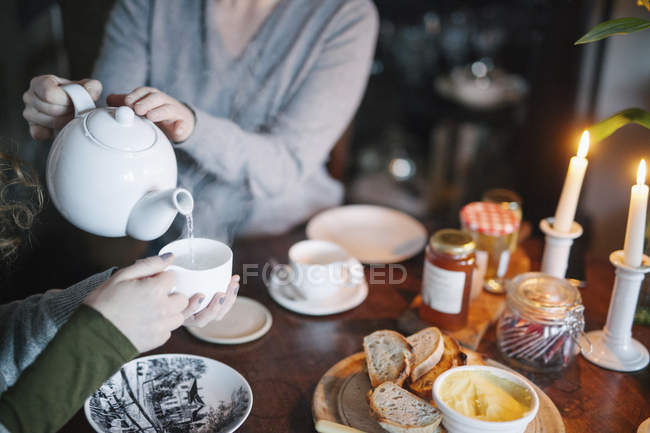 Woman pouring tea from a teapot — Stock Photo