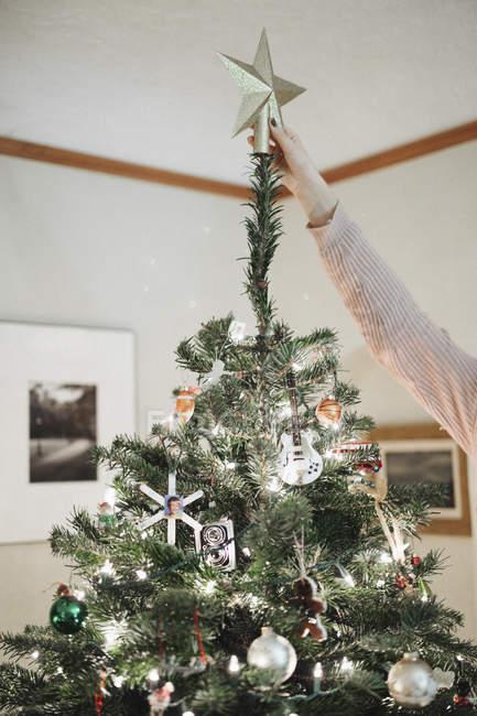 Person, die einen Weihnachtsbaum Dekoration — Stockfoto
