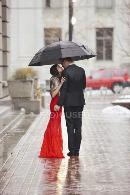 Casal beijando sob um guarda-chuva em uma rua . — Fotografia de Stock