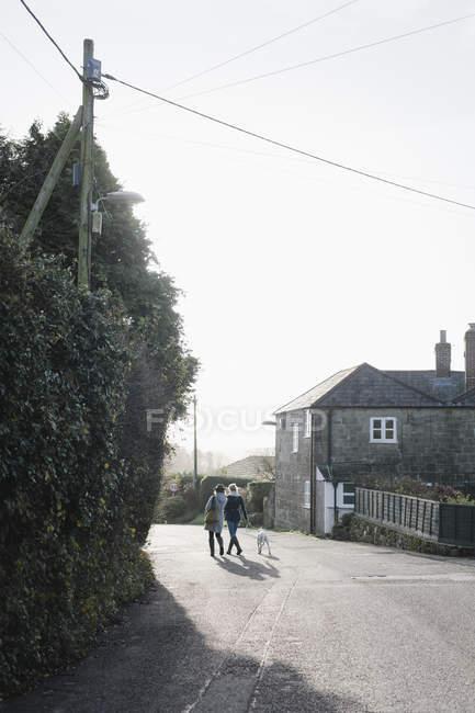 Mulheres andando com um cachorro — Fotografia de Stock