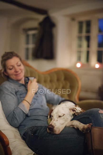 Mulher sentada num sofá com o cachorro — Fotografia de Stock