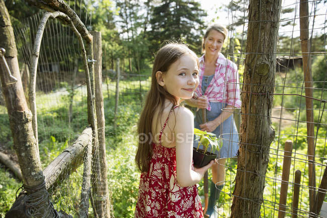 Woman and child working together in garden — Stock Photo