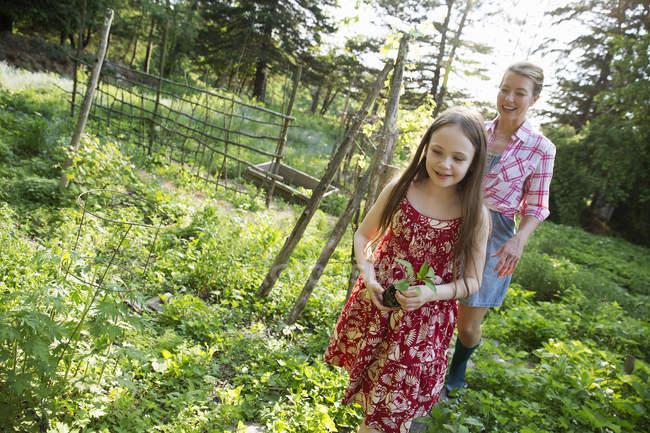 Girl walking through gardens with woman — Stock Photo