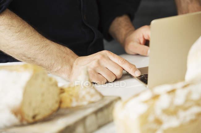 Пекарь с помощью ноутбука — стоковое фото